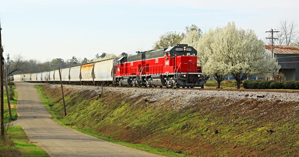 Red GP15 locomotive from LTEX #1449, passing by an orchard in bloom.