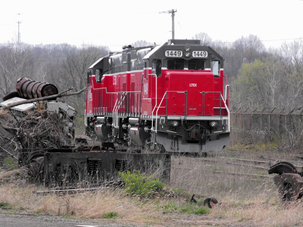 Red LTEX GP15 locomotive, all alone and passing by an old junked prime mover