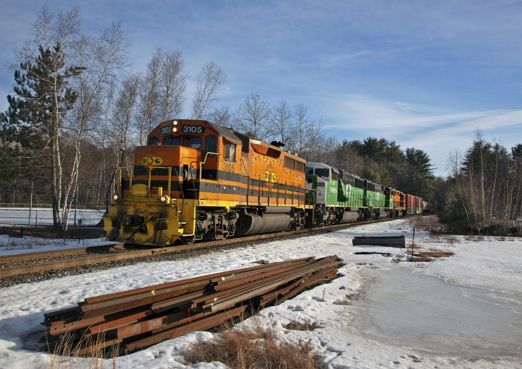 Q&G orange GP40 loco linked to green loco in the winter, spare railroad ties lie beside the track