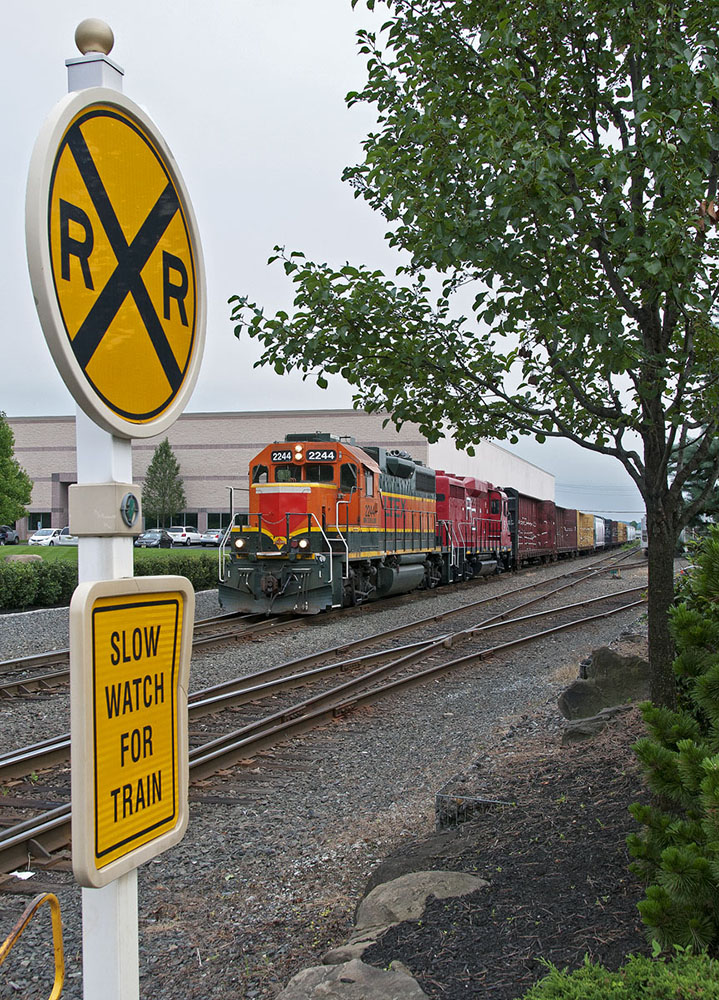 GP38 from LTEX Orange red Black yellow at a Railroad crossing, Yellow crossing sign in front